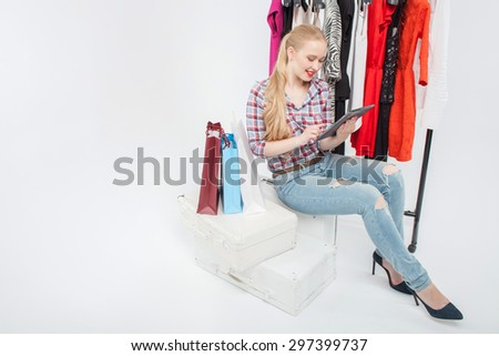 Attractive blond woman is sitting in store and holding laptop. She is looking at it with interest and smiling. There are racks of clothing and packets near her. Isolated and copy space in left side - stock photo