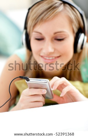 Attractive blond woman listening music lying on a sofa in the living-room - stock photo