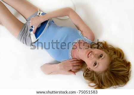 Attractive blond woman lying on the floor with a clothing iron on stomach as if ironing it to make it flat - stock photo