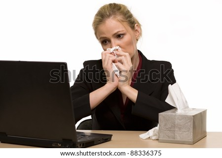 Attractive blond woman secretary sitting at office desk with a box of tissues on the desk while blowing her nose - stock photo