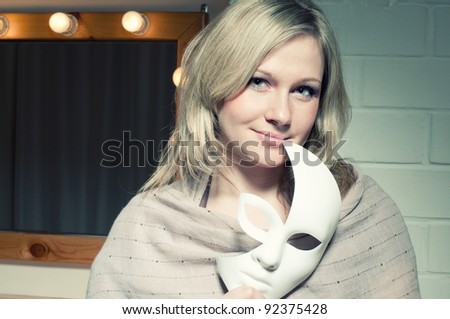 Attractive blond woman with a face mask smiling and looking at camera - stock photo