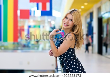 attractive blond woman with credit cards in shopping mall - stock photo
