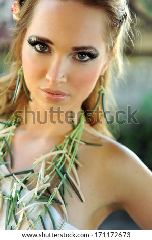 Attractive Blond woman with green bamboo nacklace on her chest - stock photo