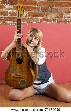 Attractive blond woman with guitar near brick wall - stock photo