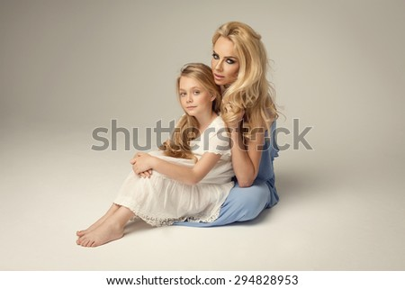Attractive blond woman with her daughter - stock photo