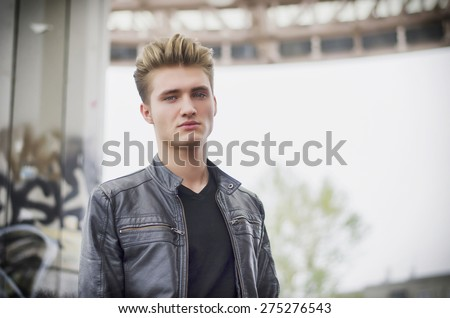 Attractive blond young man in city environment, looking down at camera - stock photo