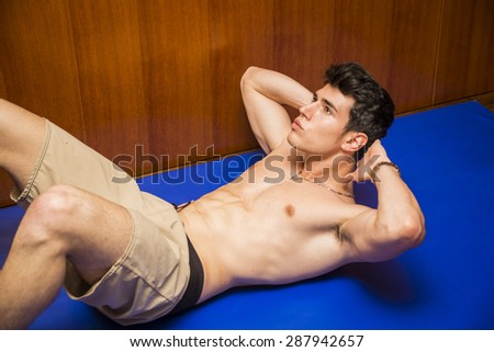 Attractive blond young man shirtless in gym working out, doing exercises for abs - stock photo