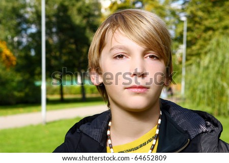 Attractive blonde boy posing and have fun in park - stock photo