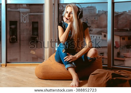 Attractive blonde girl listening to the music in headphones and looking at camera. Girl listening to the music. Blonde listen to the music in headphones. Music in headphones. - stock photo