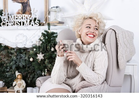 Attractive blonde girl sitting in a chair. Knitted stylish clothes. Bright charming smile. Series of winter holiday photos. Merry Christmas and Happy New Year! - stock photo