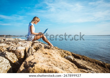 Attractive blonde hair woman working with a laptop on the seashore and look to the laptop. Female freelancer working near the sea. - stock photo