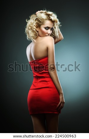 Attractive blonde in a red (green background) - stock photo