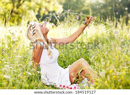 Attractive blonde lying in the field and holding flower in hand - stock photo
