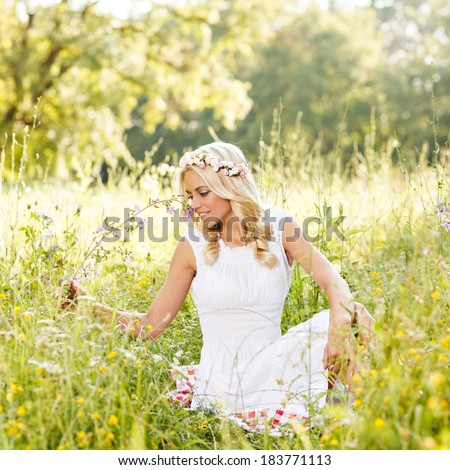 Attractive blonde lying in the field and holding flower in hand. Selective focus on face. - stock photo