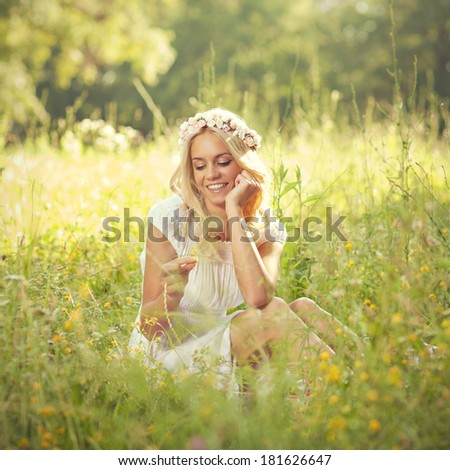 Attractive blonde lying in the field and holding flower in hand. Toned image. - stock photo