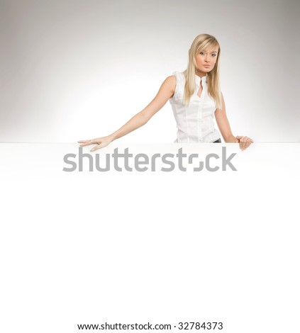 Attractive blonde secretary over white empty board, lots of copyspace - stock photo