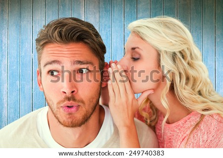 Attractive blonde whispering secret to boyfriend against wooden planks - stock photo