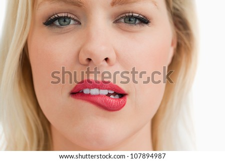 Attractive blonde woman biting her lips against a white background - stock photo