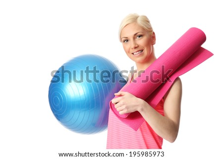 Attractive blonde woman holding a blue gym ball and pink yoga mat, wearing a pink top. White background. - stock photo
