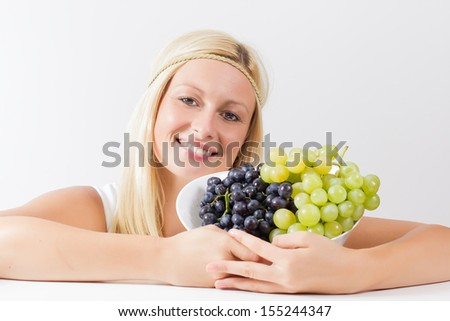 Attractive blonde woman holding grapes. - stock photo