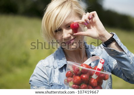 Attractive blonde woman holding up large a ripe red strawberry in her fingers from a punnet full that she is holding outdoors in sunshine - stock photo