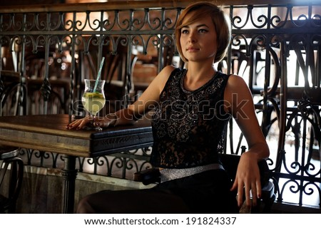 Attractive blonde woman in elegant black dress sitting on bar stool. Gorgeous blonde model posing provocatively in vintage bar - stock photo