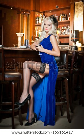 Attractive blonde woman in elegant blue long dress sitting on bar stool holding a glass in her hand. Gorgeous blonde model showing her long legs in black stockings drinking and posing in vintage bar - stock photo