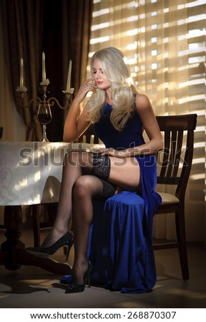 Attractive blonde woman in elegant long dress sitting near a table in a luxurious classic interior. Gorgeous blonde model showing her long legs in black stockings. Sensual lady in a vintage scenery - stock photo