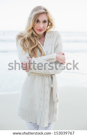 Attractive blonde woman in wool cardigan looking at camera on the beach - stock photo