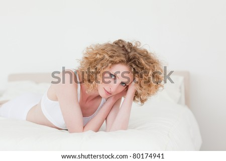 Attractive blonde woman relaxing while lying on her bed in her apartment - stock photo