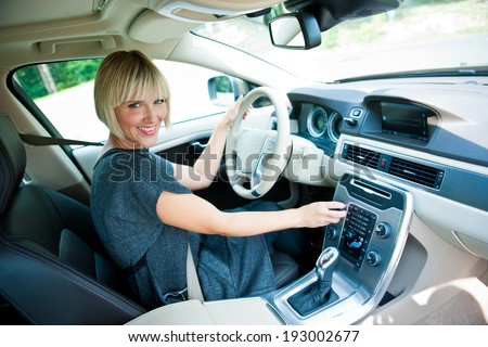 attractive blonde woman smiling at driver seat in her car - stock photo