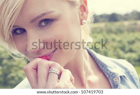 Attractive blonde woman standing outdoors in an agricultural field enjoying a ripe strawberry which she has just picked - stock photo