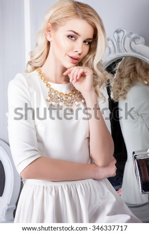 Attractive blonde woman with light gentle makeup on her face, curly locks fall on your face, light clothing and classic interior in the background.The girl in a beautiful jewelry on the neck. - stock photo