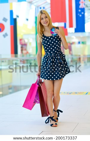 attractive blonde woman with shopping bags holding credit card - stock photo
