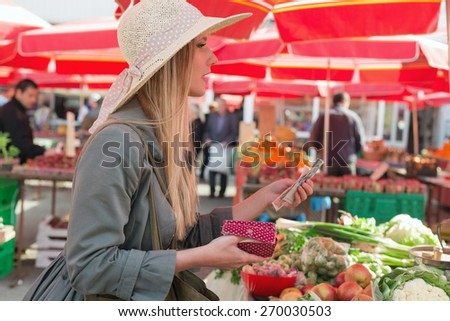Attractive blonde woman with straw hat paying vegetables on marketplace. - stock photo