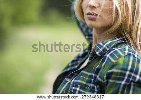 Attractive blonde women wearing a green shirt, blonde hair on green background - stock photo