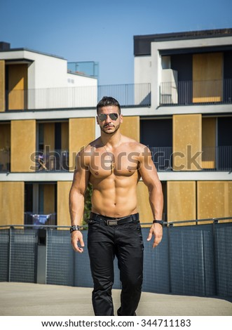 Attractive bodybuilder shirtless with baseball hat showing torso muscles, abs, pecs and arms, looking at camera - stock photo