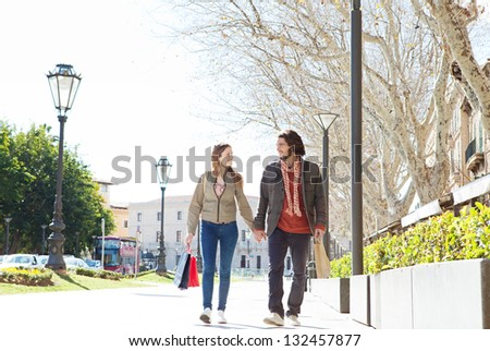 Attractive bohemian couple holding hands and walking together carrying shopping bags while on vacation in a destination city. - stock photo