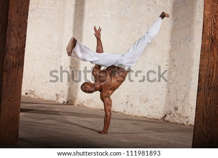 Attractive Brazilian man performing a capoeria kick - stock photo