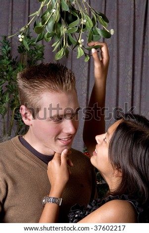 Attractive brunette asking for a kiss under the christmas mistletoe - stock photo