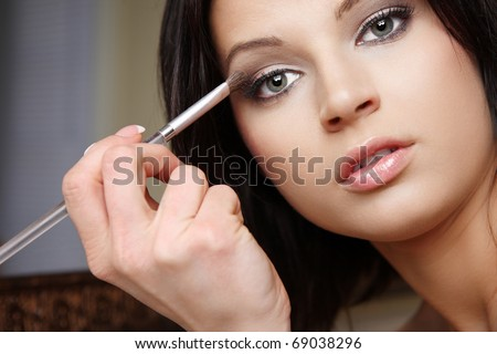 Attractive brunette doing make-up. - stock photo