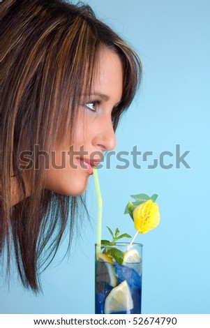 Attractive brunette drinking a blue cocktail with a straw - stock photo