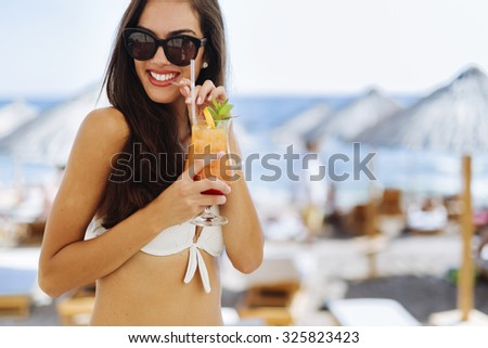 Attractive brunette drinking cocktails on beach and enjoying her vacation - stock photo
