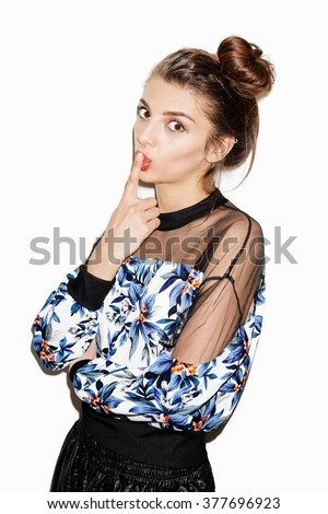 Attractive brunette girl posing for camera. Bright makeup,hairdo and casual style. White background, not isolated. Inside. - stock photo
