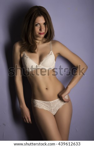 Attractive brunette in a beige lace lingerie posing near the purple wall - stock photo