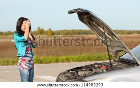 attractive brunette in front of her car broken down car - stock photo
