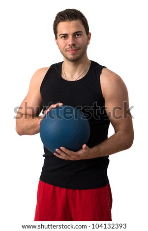 Attractive brunette man in a black tank top and red pants working out with a medicine ball - stock photo