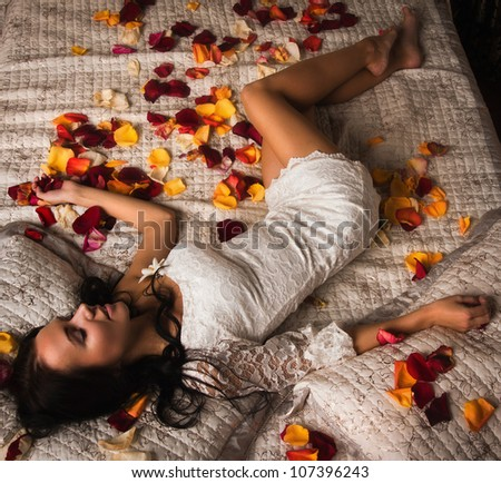 Attractive brunette sleeping on a bed in a boudoir - stock photo