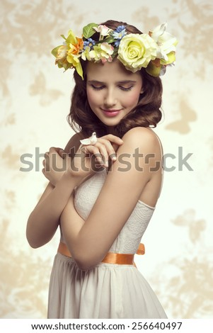 Attractive, brunette spring woman in white dress. She has got little bird on her finger and wreath of flowers on her head. - stock photo