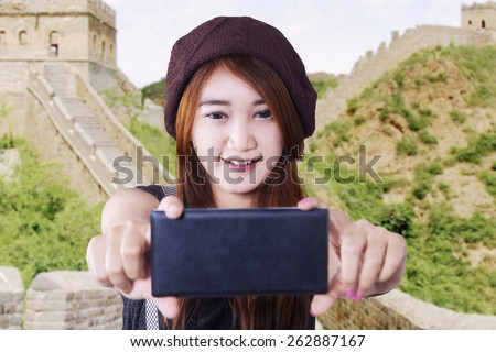 Attractive brunette teenage girl using a mobile phone to take self picture at Great Wall of China - stock photo